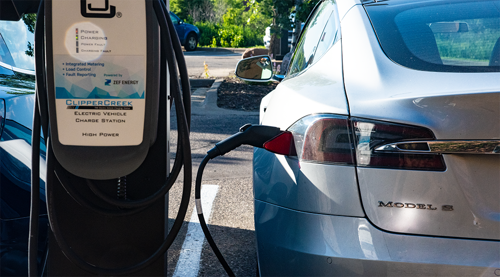 Electric car plugged into charging station used for solar synchronization pilot project