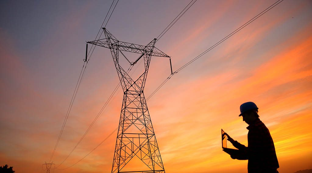 A worker standing in front of transmission lines at sunset