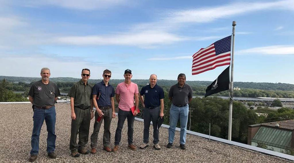 Five men standing on a rooftop