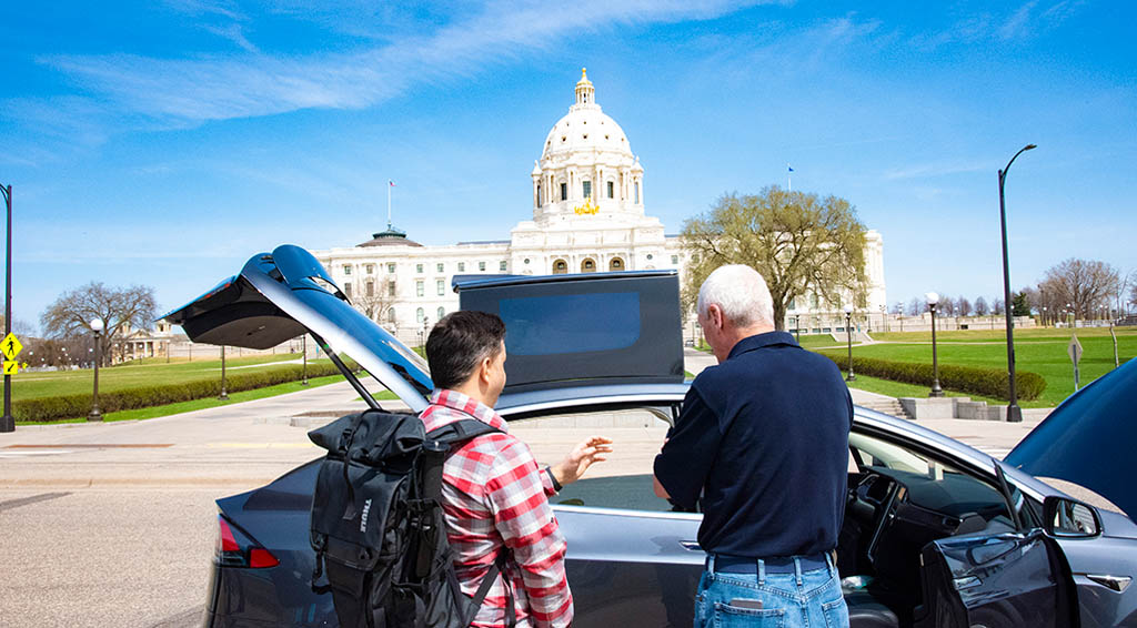 Two people talking in front of an electric vehicle in view of the minnesota state capital.