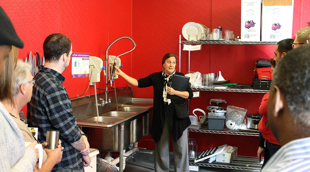 A woman demonstrating higher efficiency dishwashing in a retaurant