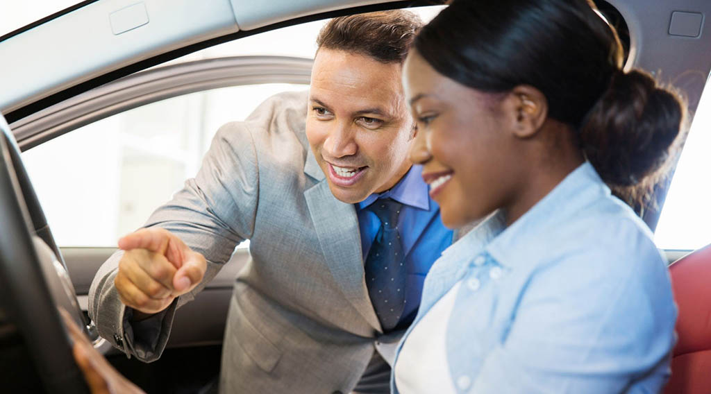 A sales person showing someone a car feature
