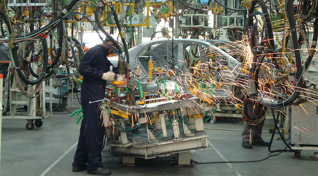 A worker machining a piece of a car body
