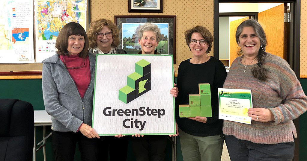 People posing with a GreenStep Cities sign