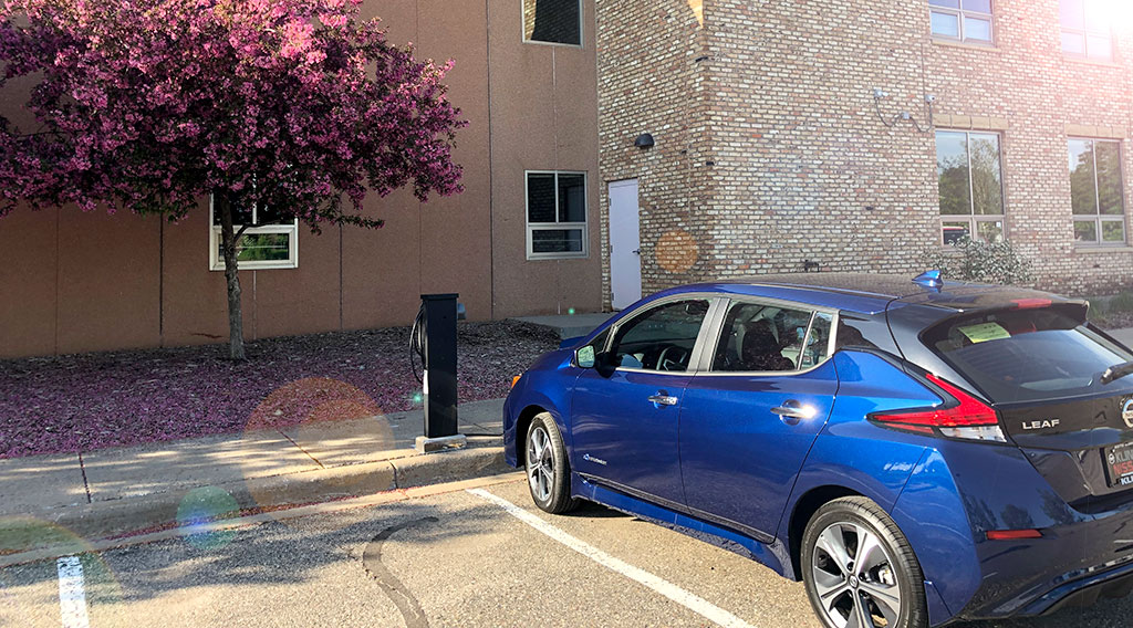 An electric vehicle charging at the greenway building